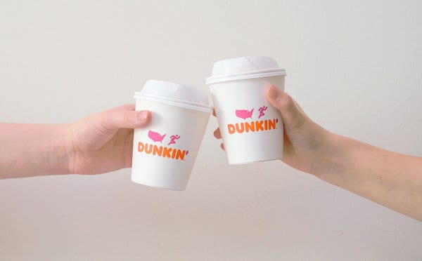 Two hands holding Dunkin' Donuts beverage cups