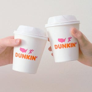 Two hands holding Dunkin' Donuts beverage cups.