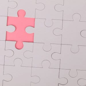 A jigsaw puzzle with one missing piece.