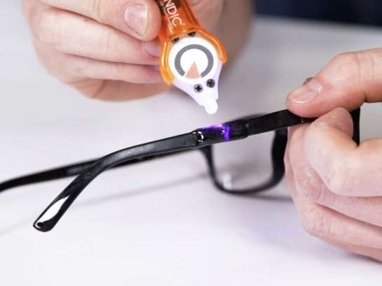 A person fixing their glasses with Bondic.