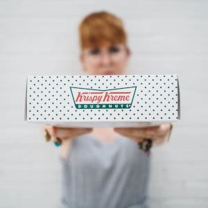 A person holding a Krispy Kreme box in front of them.