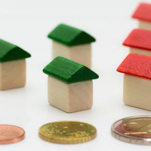 House figurines with coins in front of them, symbolizing home equity.