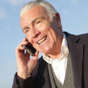 A senior man speaking on the phone.