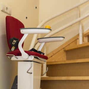 A fully set-up stairlift with the rail system visible.