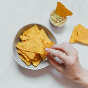 A person picking a tortilla chip from a bowl.