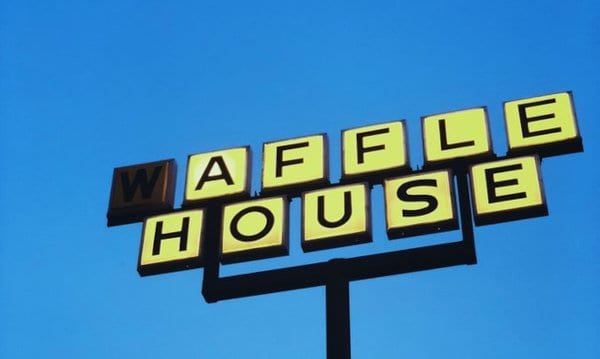 A traffic sign of a Waffle House location.