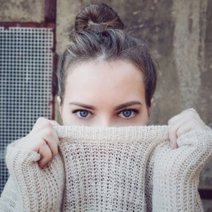 A person with blue eyes covering their mouth with their sweater.