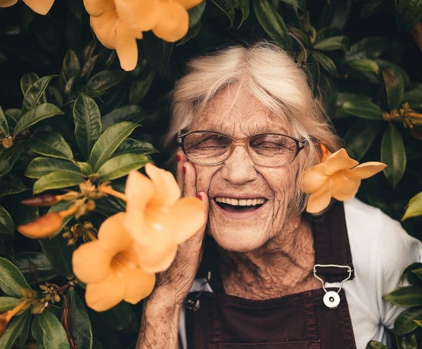 A smiling senior woman against a background of flowers.