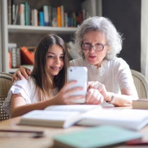 A girl showing something on her phone to her grandmother.