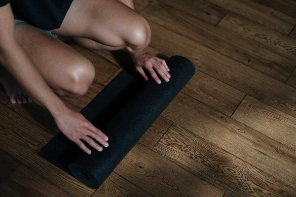 A person leaning onto a yoga mat.