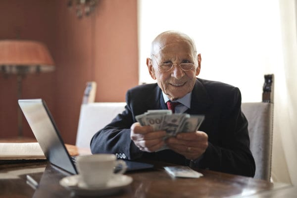 A senior person holding cash.