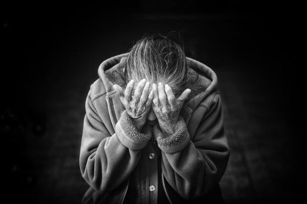 A senior person holding their head in what appears to be grief.